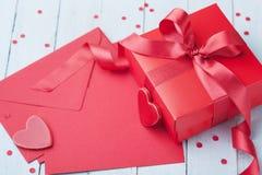 Busta, regalo, carta di carta e cuore rosso sulla tavola blu per accogliere il giorno dei biglietti di S. Valentino Immagini Stock Libere da Diritti