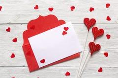 Busta rossa con la carta in bianco e cuori sul backgrou di legno bianco Fotografia Stock