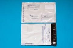 Busta russa del polietilene della posta su fondo blu Borse di spedizione postali di plastica immagini stock