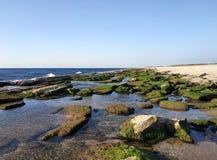 Bustan HaGalil sandy beach with rocks near Acre Haifa Israel. Akko seashore Mediterranean sea. Clear water stones. Bustan HaGalil sandy beach with rocks near royalty free stock photos