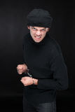 Busted burglar. Angry burglar in handcuffs grimacing at camera while standing against black background stock photo