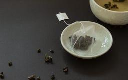 Bustina di tè in piattino su fondo nero Immagini Stock