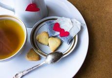 Bustine di tè con cuore biscotti della prima colazione sotto forma di cuori St Giorno del ` s del biglietto di S Immagini Stock Libere da Diritti
