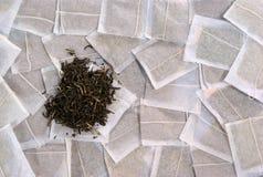 Bustine di tè e un mucchio di tè verde immagine stock