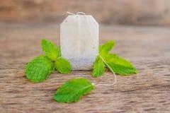 Bustine di tè su fondo di legno con melissa fresca, menta Tè con Fotografia Stock Libera da Diritti