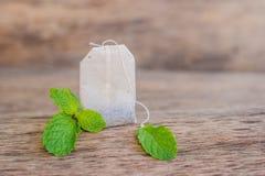 Bustine di tè su fondo di legno con melissa fresca, menta Tè con il concetto della menta Immagini Stock