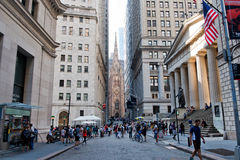 Bustling Wall Street Scene, New York City, USA. View of Wall Street Crowded with People and Looking Toward Broadway and Trinity Church - Urban New York City stock image