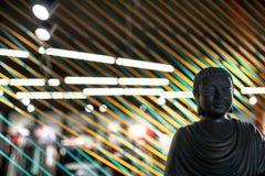 Busto de Buda en interior iluminado con las líneas coloridas instalación de las cuerdas fotografía de archivo