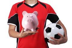 Busto fêmea no uniforme do futebol que guarda um mealheiro fotografia de stock royalty free