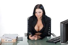 Busty Büroangestellter, der ein Mobiltelefon anhält Lizenzfreie Stockfotografie