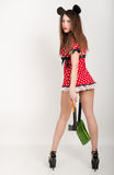 Busty beautiful young girl in a short dress with polka dots, bear in one hand and a shovel in the other  ax, back view Royalty Free Stock Photo