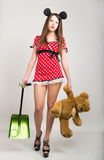 Busty beautiful young girl in a short dress with polka dots, bear in one hand and a shovel in the other teddy bear Royalty Free Stock Photography
