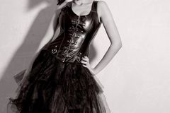Busty girl in leather corset. Young dominant woman stands near the wall stock images