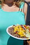 Busty Mädchen, das geschmackvolle Paella zeigt Stockfotografie