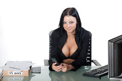 Busty office worker holding a cellphone Royalty Free Stock Photography