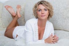 Busty schönes Mädchen, das auf dem Sofa liegt Stockbilder