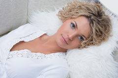 Busty schönes Mädchen, das auf dem Sofa liegt Lizenzfreies Stockfoto