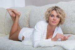 Busty schönes Mädchen, das auf dem Sofa liegt Stockfotografie