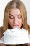Busty sexy girl eating cake with whipped cream Royalty Free Stock Photo