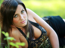 Busty spring girl. Busty cleavage young female girl or woman in spring on or in front of a nice summer green grass meadow with a shirt and braless Stock Photography