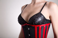 Busty woman in black bra and corset Stock Images
