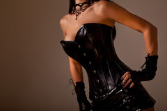 Busty woman in black leather corset. Close-up shot of busty woman in black leather corset, studio shot on golden background stock photography