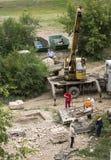 Busuluk, Rusland - Juli 7, 2014: de bouw Een kraan heft grav op Stock Fotografie