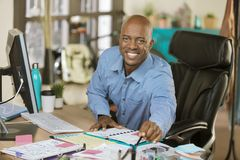 Busy African American Business Man in Office. Busy professional man working in a creative office Stock Images