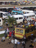 Busy African bus station in Kumasi, Ghana. Passengers wait as cargo and baggage is loaded onto minivans at crowded Kejetia Station in Kumasi, Ghana Royalty Free Stock Photo