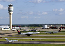 Busy airport. Busy Atlanta, Hartsfield Jackson Airport with Delta jets taking off, business jet in foreground and control tower in background Royalty Free Stock Photo