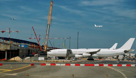 Busy airport , construction and developing. The modern busy airport - airplanes are parked & flying in the sky, development and construction in progress Royalty Free Stock Image