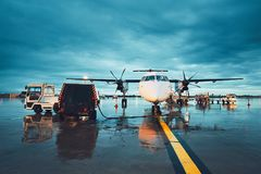 A busy airport in the rain. Preparation of the propeller airplane before flight Royalty Free Stock Images