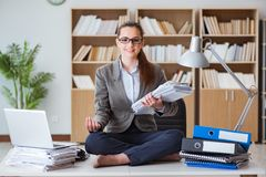 The busy angry businesswoman sitting on the desk in office Royalty Free Stock Photography