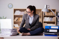 The busy angry businesswoman sitting on the desk in office Stock Image