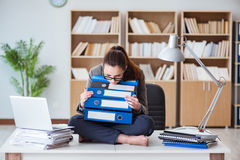 The busy angry businesswoman sitting on the desk in office Royalty Free Stock Images