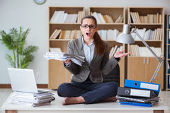 The busy angry businesswoman sitting on the desk in office Stock Photo