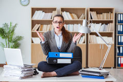 The busy angry businesswoman sitting on the desk in office Stock Photos