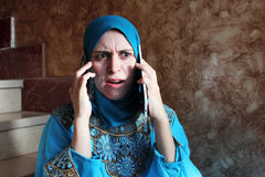 Busy arab muslim businesswoman with tablet and mobile Stock Images