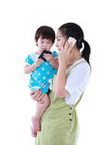 Busy asian mother using smartphone and carrying her daughter.  I Royalty Free Stock Photo