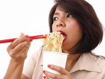 Busy Asian woman eating instant noodles Royalty Free Stock Photography