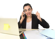 Busy attractive woman in business suit working in stress desperate overwhelmed. Busy attractive woman in business suit working in stress desperate talking on Royalty Free Stock Photography