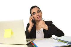 Busy attractive woman in business suit working in stress desperate overwhelmed. Busy attractive woman in business suit working in stress desperate talking on Royalty Free Stock Photos