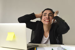 Busy attractive woman in business suit working in stress screaming desperate overwhelmed Royalty Free Stock Photo