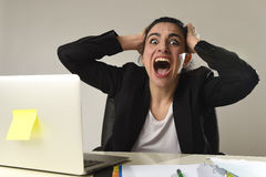 Busy attractive woman in business suit working in stress screaming desperate overwhelmed Stock Photo