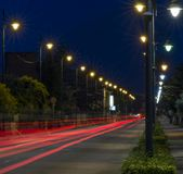Busy avenue with light trails of cars in the blue hour. And street lamps Stock Photo
