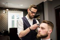 Busy barber shaving customer hair. Portrait of busy barber shaving customer hair Stock Image