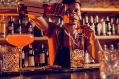 Busy barman making cocktails for clients at night. Cocktails for clients. Busy barman wearing uniform making cocktails for clients at night stock photos