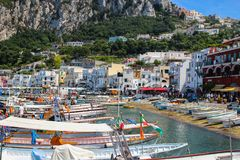 Busy beach with boats docked and people walking in the island of. Capri, Italy 2015-06-27 Busy beach with boats docked and people walking in the island of Capri royalty free stock photo
