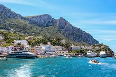 Busy beach with boats docked and people walking in the island of. Capri, Italy 2015-06-27 Busy beach with boats docked and people walking in the island of Capri stock image