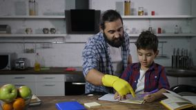 Busy single father helping his son with homework. Busy bearded stay-at-home father helping elementary age son with homework for primary school while doing stock video footage